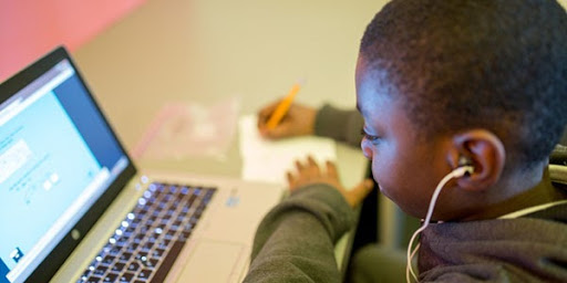 Child listening to headphones and taking notes from laptop study