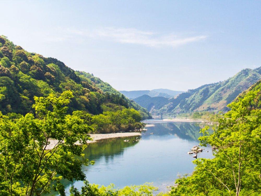 翠綠山色倒映在日本清澈的四萬十川上,景色優美。