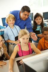Computer class teacher helping students