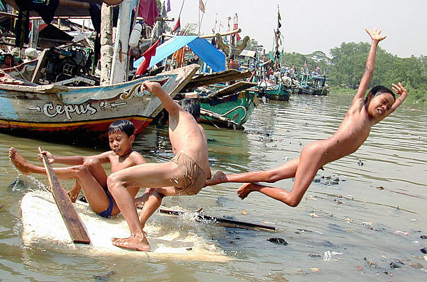 young-boys-play-at-a-river-littered-with-rubbish-in-north-jakarta-14-picture-id2588706.jpg (혐) 인도인들의 성수 겐지스 강 실태.jpg