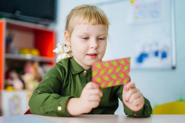 Adorable joven está mirando una tarjeta brillante. concepto de preescolar. educación infantil. Foto Premium