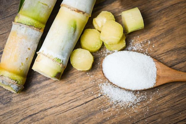 Cortar el pedazo de caña de azúcar y el azúcar blanco en una cuchara de  madera | Foto Premium