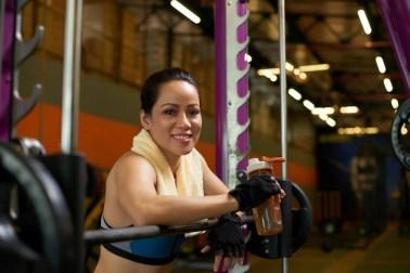Deportista alegre sonriendo a la cámara en la máquina smith en un gimnasio Foto gratis