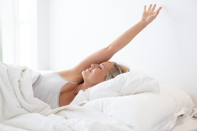Feliz joven se extiende en la cama después de dormir Foto gratis