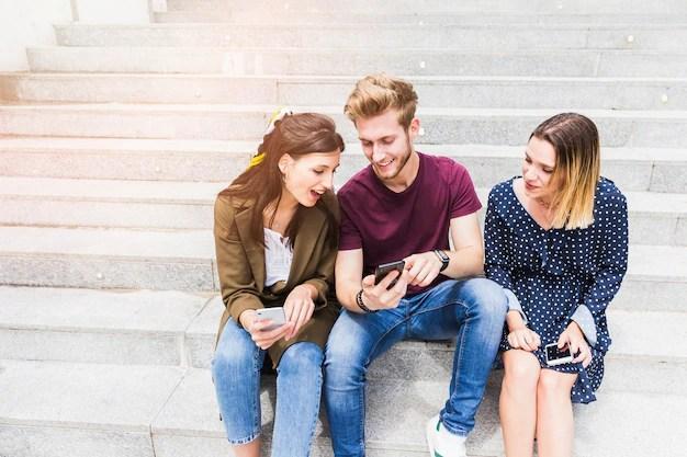 Grupo de amigos mirando la pantalla del teléfono.