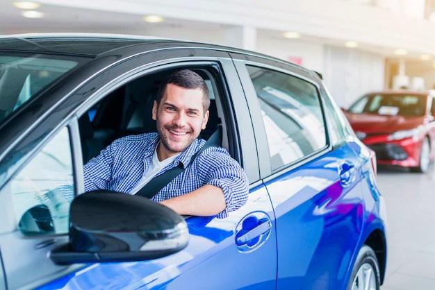 Hombre en coche en concesionario Foto gratis