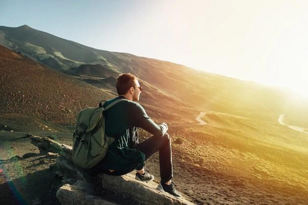 Hombre con mochila sentado en la roca al atardecer en el volcán etna montaña en sicilia Foto gratis