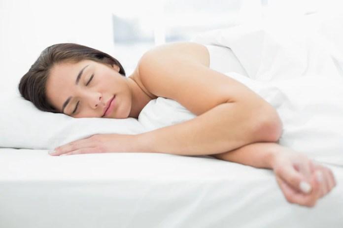 Linda mujer durmiendo en la cama | Foto Premium