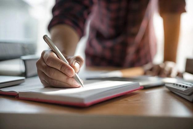 Mano de empresarios sosteniendo la pluma al escribir notas en el ...