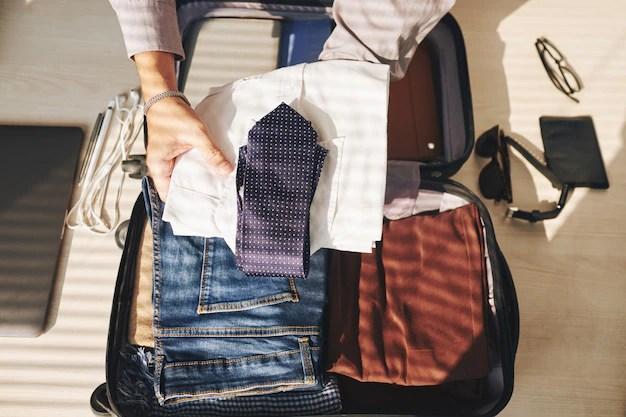 Manos de hombre irreconocible empacando maleta para viajar Foto gratis