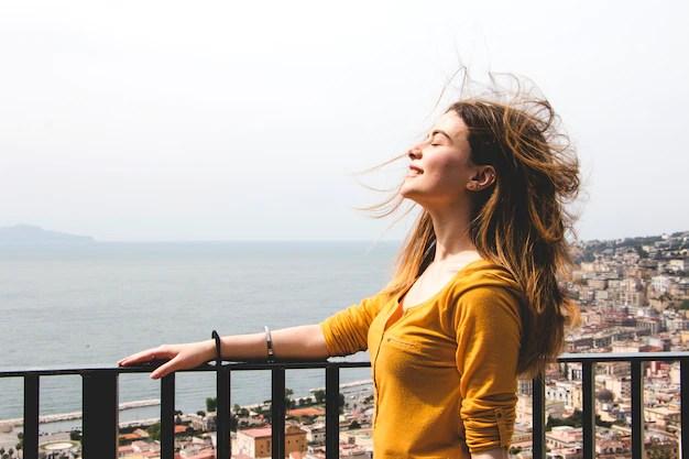 Mujer disfrutando aliento de viento Foto gratis