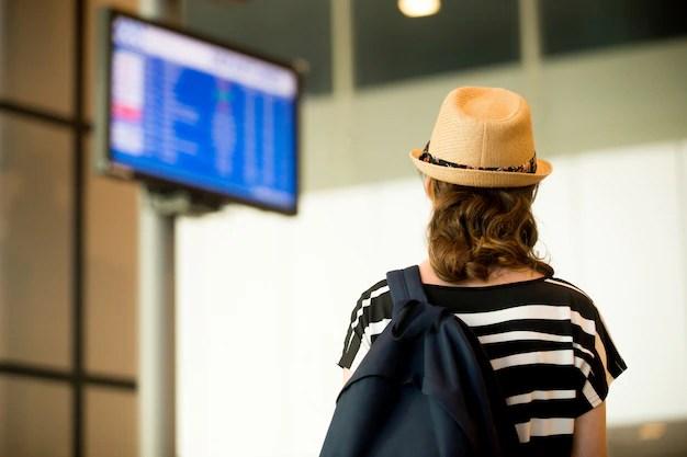 Mujer mirando pantallas en el aeropuerto Foto gratis