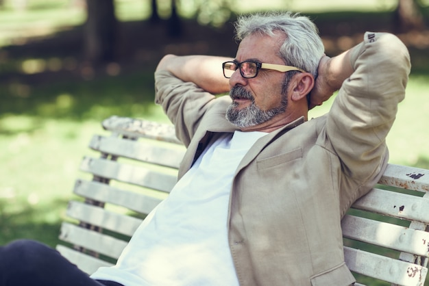 Pensive hombre maduro sentado en el banco en un parque urbano. Foto gratis