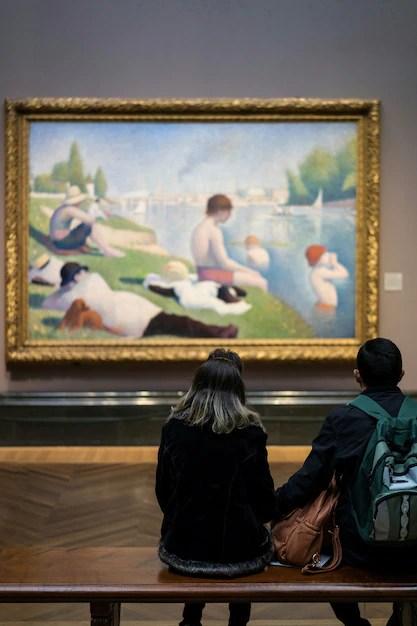 Personas que buscan una foto en la galería de arte. Foto gratis
