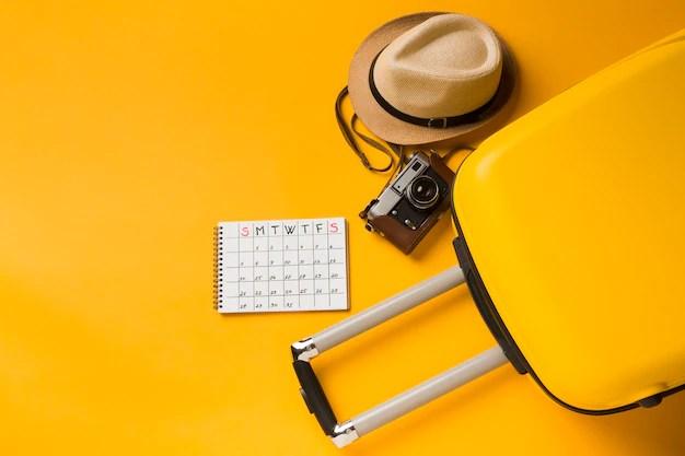 Plano de equipaje con sombrero y elementos esenciales de viaje Foto gratis