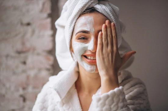 Retrato de una mujer con una máscara facial media cara Foto gratis