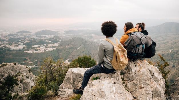 Tres excursionistas hombres y mujeres sentados en la cima de la roca con vistas al paisaje urbano y la montaña Foto gratis