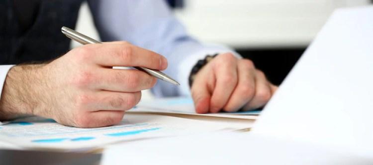 Impiegato sul posto di lavoro in ufficio con la penna d'argento tra le braccia Foto Premium