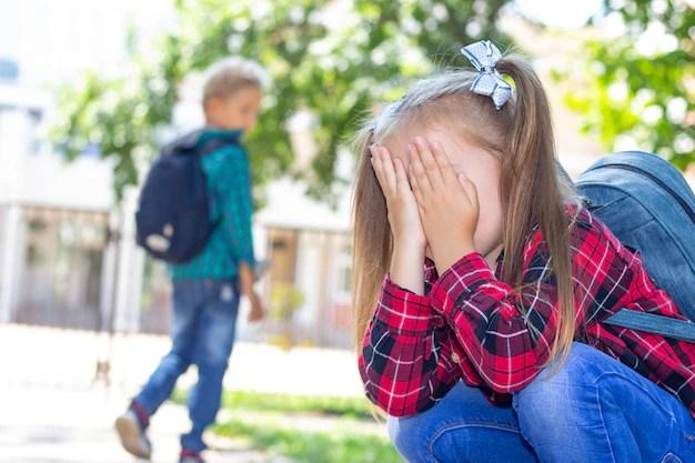 Menina escondendo rosto com as mãos na entrada da escola