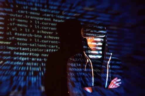 Ataque cibernético com hacker encapuzado irreconhecível usando realidade virtual, efeito de falha digital Foto gratuita