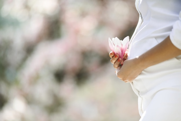 Barriga de uma mulher grávida e uma flor