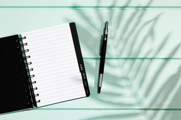 Caderno aberto e caneta em mesa