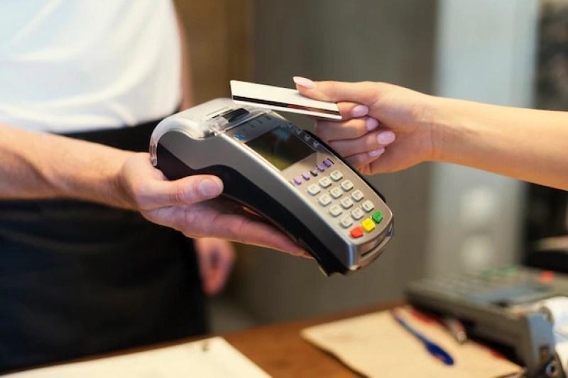na imagem close de cliente pagando com cartão de crédito | O Guia do Cartão de Crédito