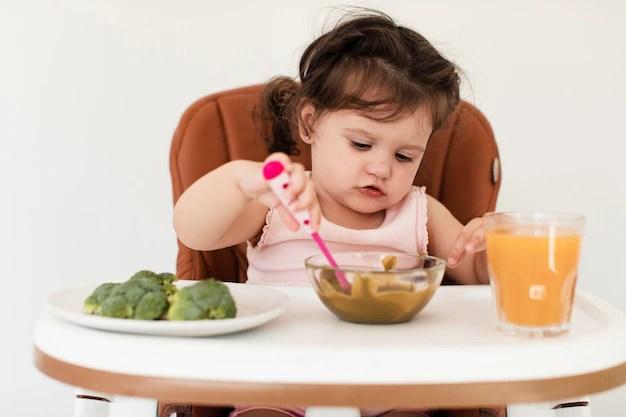 Menina sentada em cadeirinha tentando comer