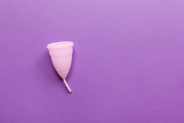 Coletor menstrual rosa em fundo roxo. Produto ideal para menstruação adiantada.