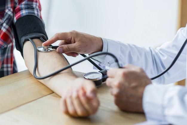 Crop doctor medindo a pressão arterial do paciente Foto gratuita