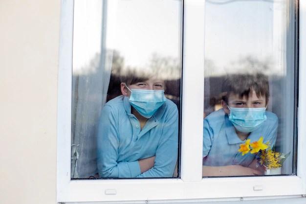 Dois meninos com máscaras de proteção olhando pela janela de casa