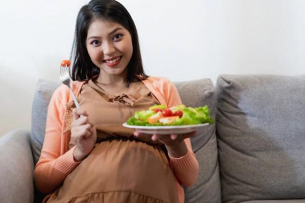 Grávida no sexto mês comendo salada no sofá