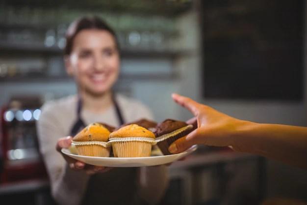 Garçonete servindo um prato de queque para o cliente Foto gratuita