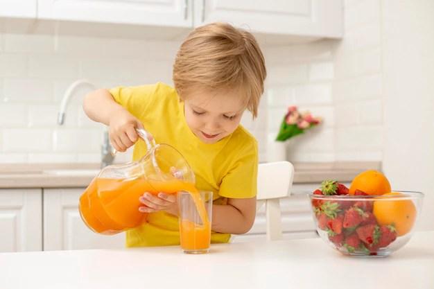 Garotinho em casa derramando suco Foto gratuita