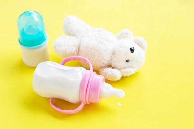 Mamadeiras com leite materno e urso de pelúcia. Dicas para secar o leite materno.