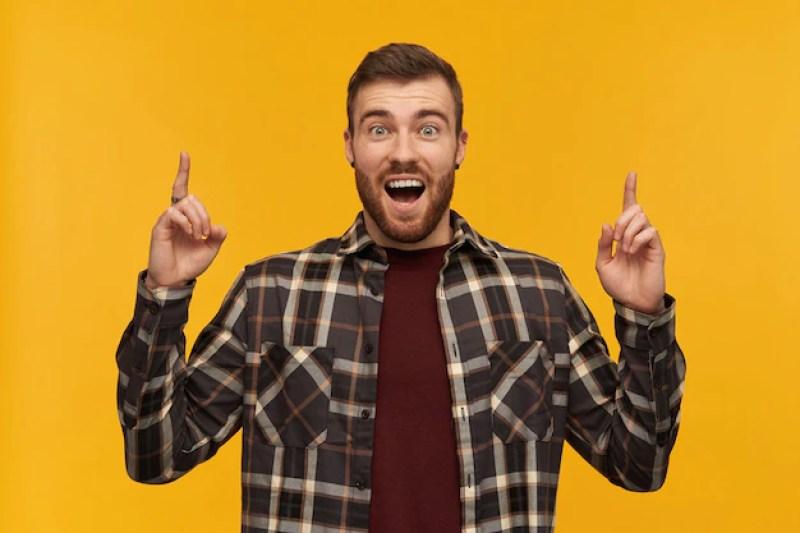 Jovem barbudo surpreso e animado com uma camisa xadrez e a boca aberta, gritando e apontando para o céu com as duas mãos sobre a parede amarela |  O guia do servidor público de como se organizar financeiramente