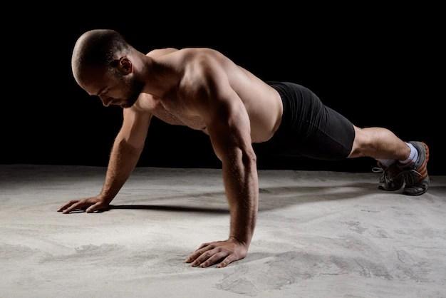 Jovem esportista poderoso treinamento flexões sobre parede escura. Foto gratuita