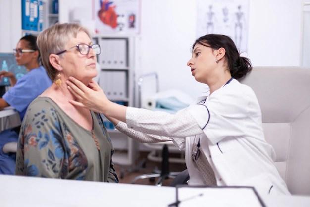 jovem-medico-palpando-o-pescoco-de-uma-mulher-idosa-paciente-idoso-visitando-o-medico-no-hospital-verificando-a-garganta-da-tireoide-tocando-a-saude-na-clinica-especialista-em-saude-medicare-conceito-medico-de-tratamento_482257-9991 Hipertireoidismo Sinais e sintomas