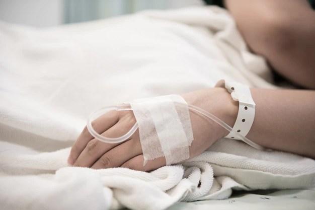 Mão de paciente mulher internada no hospital com solução salina intravenosa (iv) parto normal