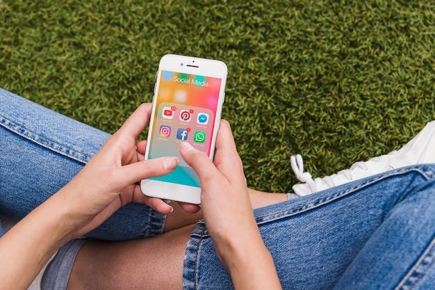 Mulher sentada na grama com celular na mão usando redes sociais