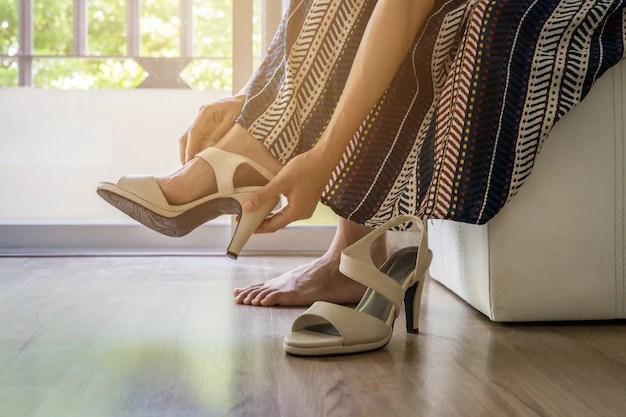 Mulher tirando sapatos de salto alto Foto Premium