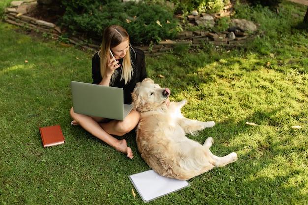 Mulher trabalhando com laptop e brincando com o cachorro labrador
