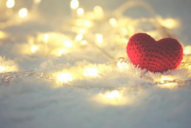 Coração de tecido em tapete felpudo branco com luzes de led no fundo