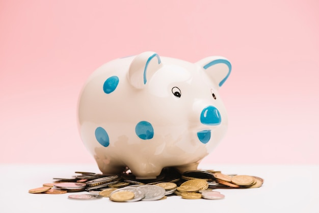 Piggybank de cerâmica manchado sobre moedas Foto gratuita