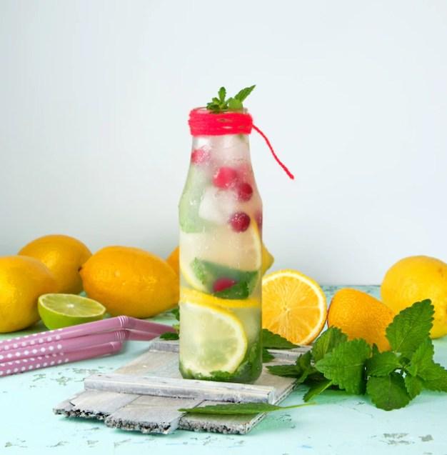 Bebida com limões, amora, folhas de hortelã em uma garrafa de vidro