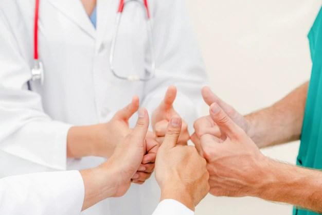 医療サービスのチームワーク - 医者、外科医、看護師が一緒に手を結ぶ。 Premium写真