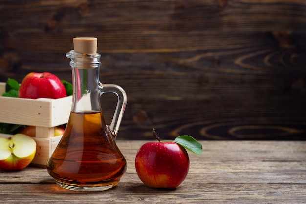 Apple cider vinegar and fresh red apple on a wooden background Premium Photo
