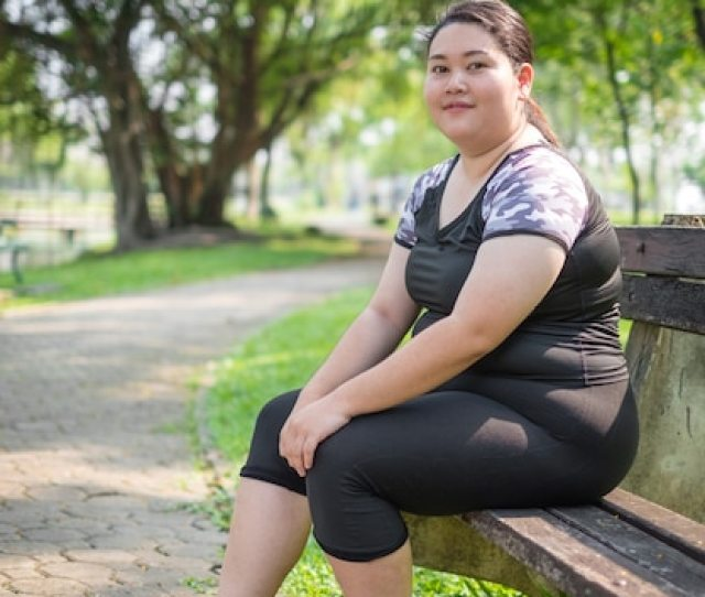 Asian Fat Woman Relaxing Exercise At The Nature Park In The Morning Premium Photo