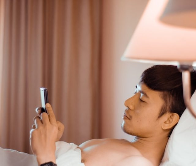 Asian Man Play Smartphone On The Bed In The Morning Premium Photo