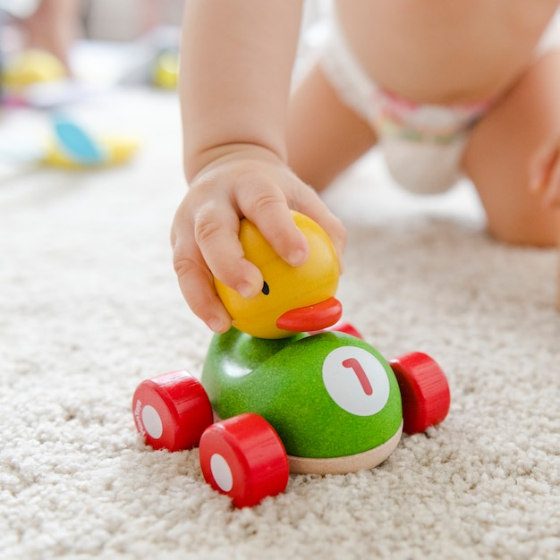 Baby playing with a wooden car Free Photo